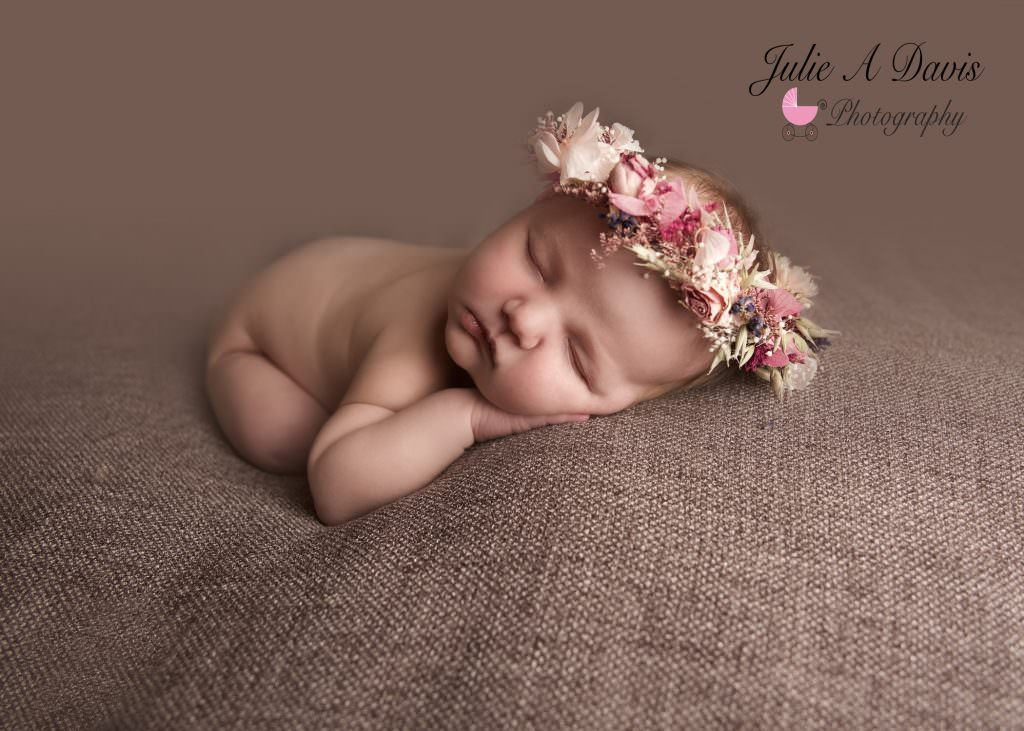 Newborn baby sleeps with beautiful flower headress by Hampshire photographer Julie A Davis